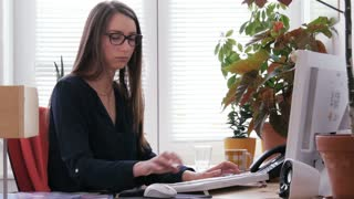 Young attractive businesswoman working on desktop computer in an office