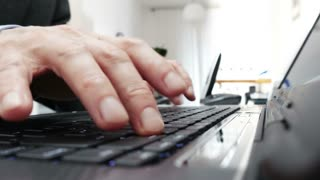 Wide angle shot of businessmans hands typing on laptop keyboard - 4k
