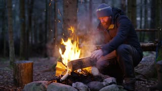 Adult man fires up campfire outdoor in the forest