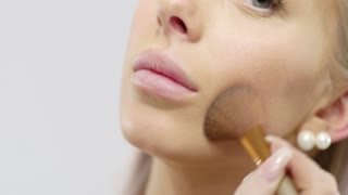 Close-up of a beautiful young woman applying dry cosmetic tonal foundation