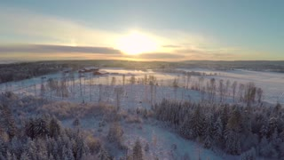 Flying above forest and farm in winter at sunset
