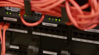 IT consultant plug in network cable in panel at datacenter