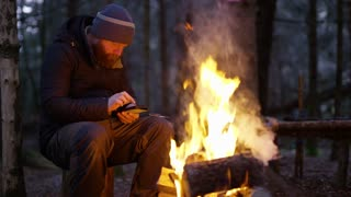 Man using compass and smart phone by campfire in the woods