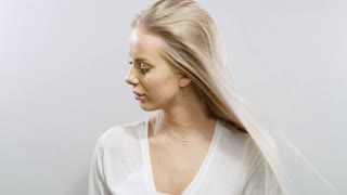Slow motion portrait of a smiling blonde woman's hair blowing in the wind