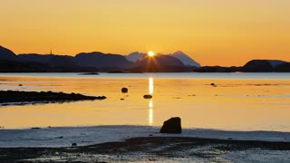 Timelapse of tide and sunset over mountain in a fjord