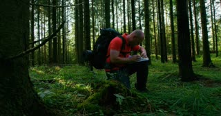 Active man hiker navigates using map and compass in beautiful forest at sunset