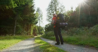 Active man with large backpack hiking in beautiful forest at sunset