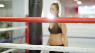 Beautiful woman tired after workout in boxing ring