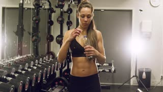 Beautiful woman with fit body walking in fitness gym
