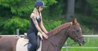 Beautiful young woman riding her arabian horse at farm