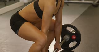 Close-up of a sporty woman training deadlift with heavy weights in fitness gym