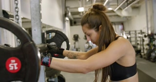 Close-up of a sporty woman training squat with heavy weights in fitness gym