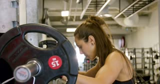 Close-up of a strong woman doing squats workout with heavy weights