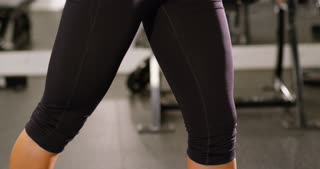 Close-up of a woman training triceps muscles pulling cable machine in gym