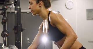 Close-up of dedicated woman training and lifting weights in fitness gym