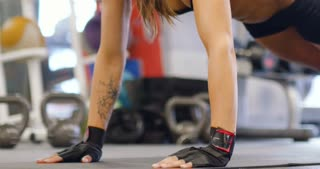 Close-up of well trained woman doing push ups at exercise mat in the gym