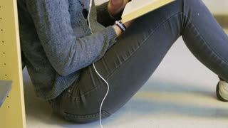 Female student sitting on the floor and reading a book in school library