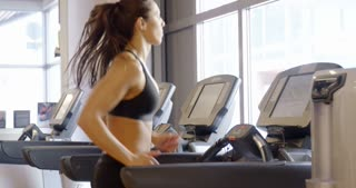 Fit woman in workout clothes running on treadmill machine in fitness gym