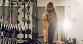Fit woman training lats and lifting weights in fitness gym