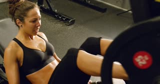 Fit woman trains legs with heavy weights in fitness gym