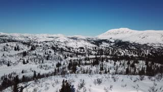 Flying in large mountain winter landscape