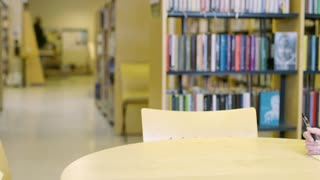 Focused female student reading books in school library