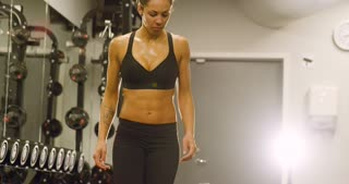 Focused fit woman training lats and lifting weights in fitness gym