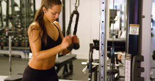 Focused woman training triceps muscles pulling cable machine in gym
