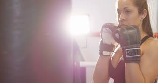 Hard hitting female boxer training in boxing club
