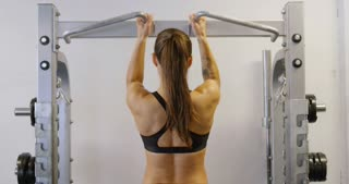 Hard training fitness woman doing heavy pull-ups in fitness gym
