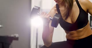 Healthy and focsued woman lifts weights at fitness gym