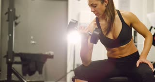 Healthy and well trained woman lifts weights at fitness gym