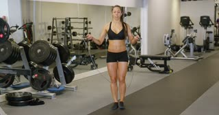 Healthy woman sweats while she jumping rope in gym