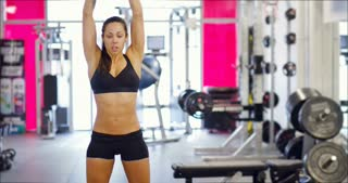 Powerful fit woman workout triceps lifting weights in gym