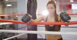 Real and powerful woman rests after workout in boxing ring