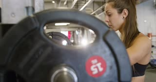 Smiling woman trains squats with heavy weights in fitness gym