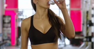 Smiling woman with fit body drinks water in fitness gym
