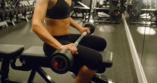 Sporty woman training chest muscles at bench machine in gym
