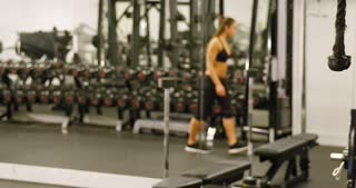 Sporty woman training triceps muscles pulling cable machine in gym