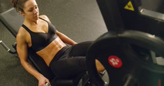 Sporty woman trains legs with heavy weights in fitness gym