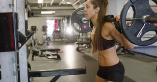Sporty woman trains squats with heavy weights in fitness gym