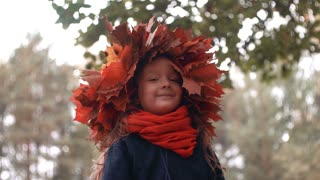4k close-up portrait of happy smiling beautiful cute little girl in a wreath crown of autumn maple leaves