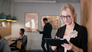 4k. closeup young beautiful blonde businesswoman uses a touchscreen tablet in the modern startup office.