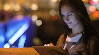 A beautiful brunette woman, using her tablet. Night city, blurred lights on the background, slow mo