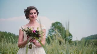 A beautiful young bride looking at her wedding bouquet standing in a wheat field. Pretty lacy wedding dress on her.