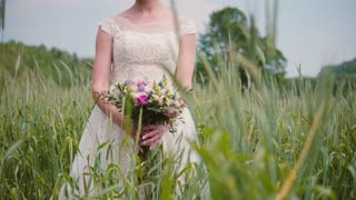 A beautiful young bride smelling her wedding bouquet standing in a wheat field. Pretty lacy wedding dress on her.