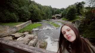 A beautiful young couple is posing for a selfie on a wooden bridge over a waterfall.