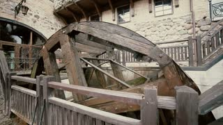 A big old watermill is working noisily inside a castle yard