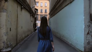 A brunette girl walking in a tunnel of buildings. Backview of a girl in a dark blue dress. Slow mo, steadicam shot