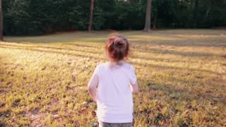 A cheerful little girl runs away from camera in a park on a sunny summer day. Back view, slow mo